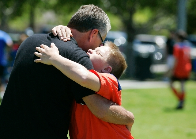 Grayson hugs his father during a game at The Crossing Park, May 11. The VIP program is offered to children 4 or older, and registration is open as long as space is available.