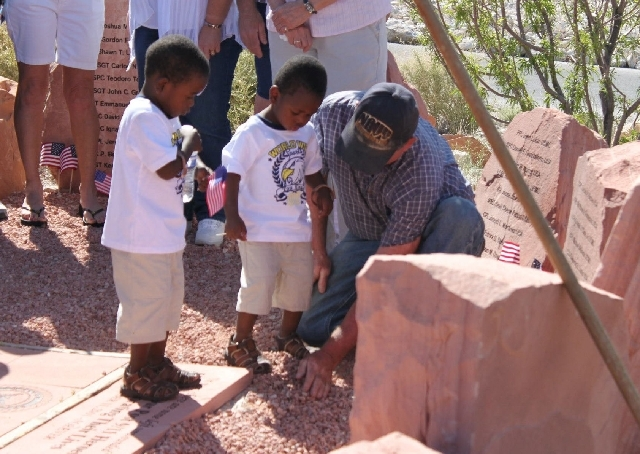 Danny Brady, kneeling, gets help from the stepsons of the late Sgt. Ezra Dawson while installing a memorial tile at the eighth annual Defending Freedom Memorial Dedication Ceremony May 4 at Red Ro ...