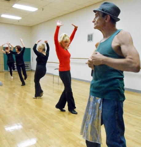 """Jonie Sailon, in red, uses her hands to give a flourish to her dance as Rich Rizzo, foreground, leads a rehearsal for the Las Vegas Follies May 15. The group plans to perform """"Sass With Class"""" at  ..."""