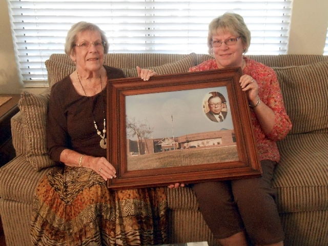 Betty White, left, and Nancy Terrell hold a photo honoring their husband and father Thurman White as a middle school namesake.