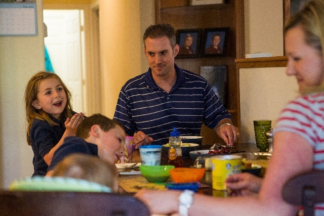 Father of three Brian Bailes, center, shares a laugh with wife, Katie, right, 8-year-old son Mitch, 6-year-old daughter Beth and 10-month-old son Luke at the dinner table in their home near Summer ...