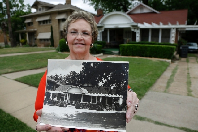 Patricia Hall poses with a circa 1960s photo of her family's boarding house, in front of the house, in Dallas. For a few weeks in 1963, Lee Harvey Oswald stayed at the red brick house with white t ...