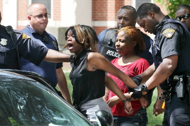 Cleveland police take a woman into custody after a fight that broke out at Michael R. White Elementary on Friday in Cleveland.  A brawl that started over spilled punch at a kindergarten graduation ...