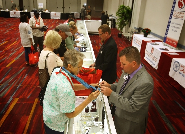 Jeremy Abee, left, with Gaston & Sheehan Auctioneer, Appraisers and Realty,holds show a costumer a piece of jewelry at the U.S. Marshals Service National Forfeited Jewelry Auction preview on Frida ...