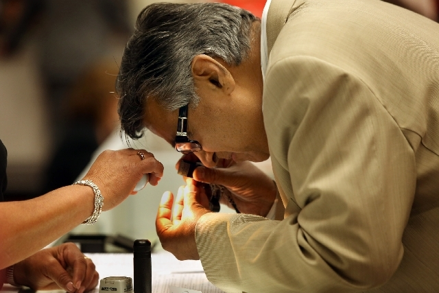 A New York man who declined to give his name looks at a loose diamond at the U.S. Marshals Service National Forfeited Jewelry Auction preview on Friday in the Las Vegas Convention Center. Over 300 ...