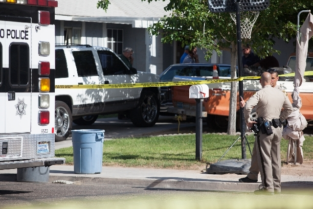 Las Vegas police officers stand by Saturday as crime scene investigators look through a house in the 5500 block of Cotton Street near Charleston Boulevard and Christy Lane where an adult and a juv ...