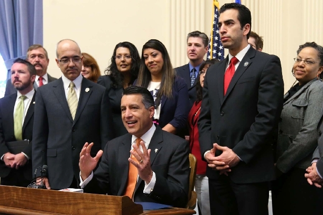 """Surrounded by legislators, Gov. Brian Sandoval speaks before signing the """"driver's authorization card"""" bill into law at the Capitol in Carson City on Friday."""