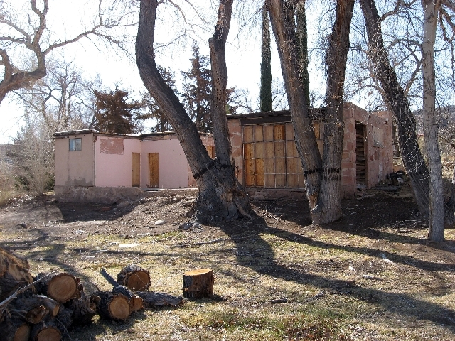 The rear of the Oliver Ranch's main house overlooked the pool and yard. The years have resulted in much damage, including deterioration to the walls and roof and missing stone siding.