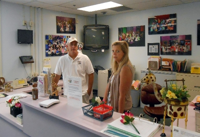 Volunteer Larry Bollinger and school clerk Nancy Bernier chat May 29 at Gilbert Magnet Elementary School, 2101 W. Cartier Ave. Bollinger, an out-of-work single father, founded the local chapter of ...