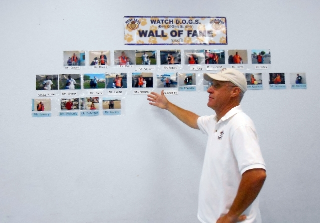Larry Bollinger shows off his volunteer Wall of Fame at Gilbert Magnet Elementary School.