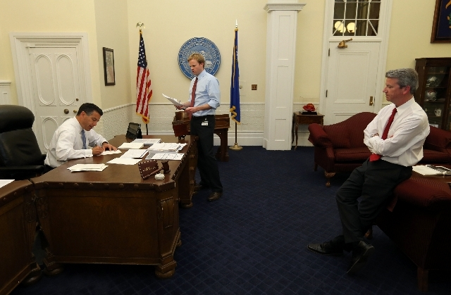 Gov. Brian Sandoval, left, signs bills Monday with intergovernmental affairs manager Tyler Klimas, center, and Chief of Staff Gerald Gardner during the final hours of the 77th Legislative session. ...