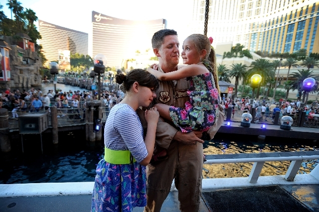 U.S. Air Force Capt. John Costa reunites with daughters Ally, left, and Tally after the Sirens of TI performance Tuesday at the Treasure Island hotel-casino. Costa returned home two weeks early to ...