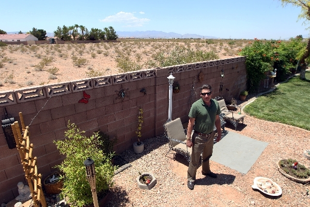Jeff Hein stands in his backyard on West Haleh Avenue in Las Vegas. The property behind him has been purchased by Lewis homes for an 80-home project.