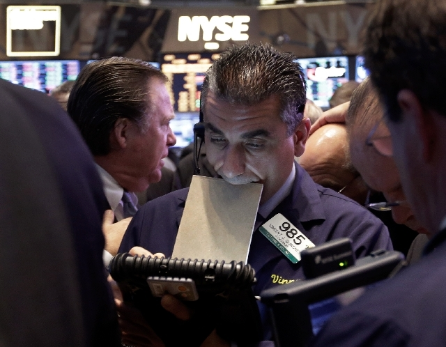 Trader Vincent Quinones, center, works on the floor of the New York Stock Exchange at the close of trading. Steady growth in hiring in May 2013 is sending the stock market sharply higher on Friday.