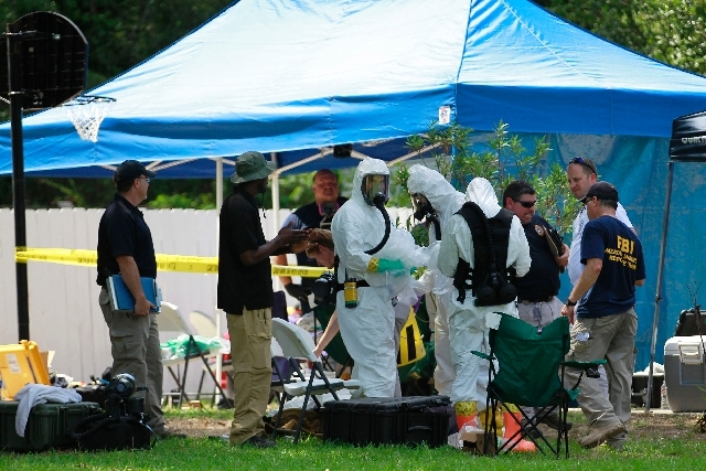 Members of an FBI hazardous materials team prepare to enter a residence in New Boston, Texas in connection with a federal investigation surrounding ricin-laced letters mailed to President Barack O ...