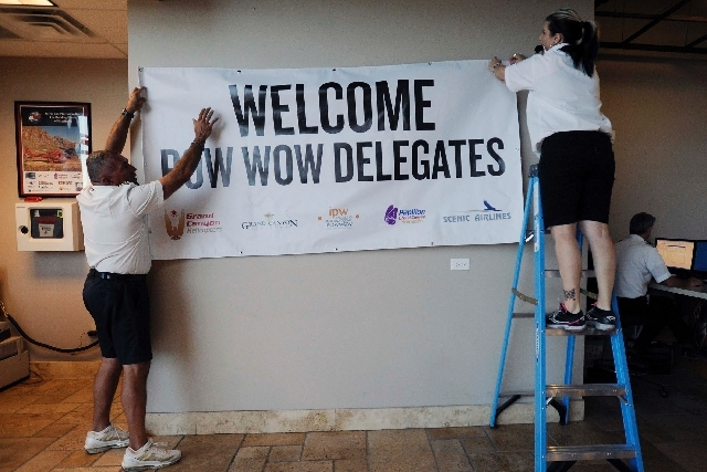 Papillon helicopter pilot Francisco Fernandez and director of customer operations Andrea Ellett on Thursday hang a banner welcoming attendees to the IPW travel conference inside the Papillon Aeroc ...