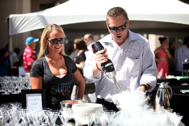 Sugar Factory bartender Molly Johnson, left, and Greg Waters, right, beverage manager, mix frozen cocktails with liquid nitrogen at the International Pow Wow press brunch at the Smith Center for t ...