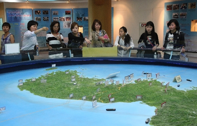 Visitors look at a relief map of Korean Peninsula at the unification observation post near the border village of Panmunjom, which has separated the two Koreas since the Korean War, in Paju, South  ...
