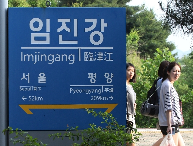 Visitors walk by a signboard showing the distance to the North Korean capital Pyongyang and that for South's capital Seoul from Imjingang Station near the border village of Panmunjom in Paju, Sout ...