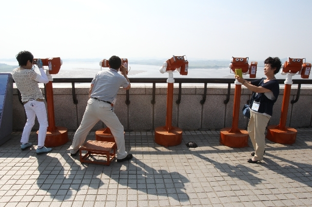 Visitors use binoculars to watch North Korean territory at the unification observation post near the border village of Panmunjom in South Korea on Monday.