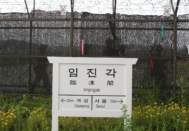 South Korean army soldiers patrol along a barbed-wire fence near directional sign showing the distance to North Korea's Kaesong city and South Korea's capital Seoul at the Imjingak Pavilion in Paj ...