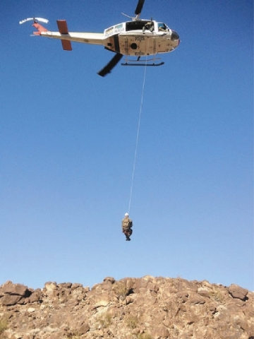 A member of the Las Vegas Search and Rescue team is hoisted by a helicopter during the search and rescue operations to find four Boy Scouts and two Scout leaders Saturday in the White Rock Canyon  ...
