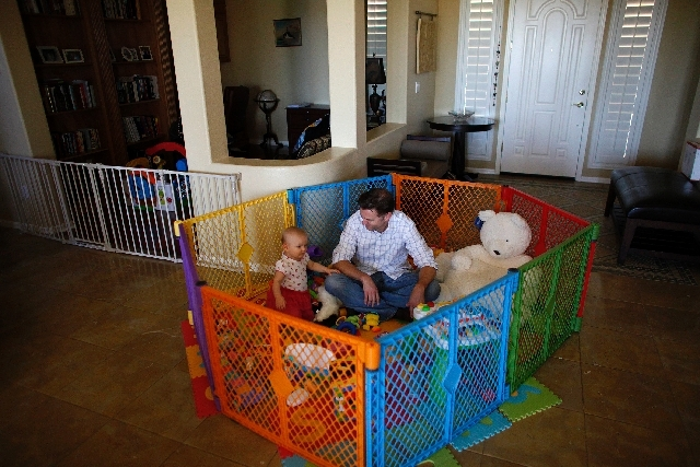 Dr. Ryan Walsh plays with his 1-year-old daughter, Eva, at their home. A nanny helps care for Eva and her brothers.