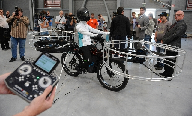 Journalists watch the remote-controlled Flying Bike with a test dummy during its presentation in Prague on Wednesday. Three Czech companies have teamed up to make a prototype of an electric bicycl ...