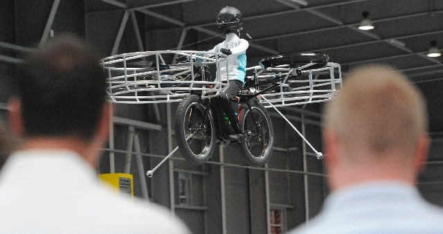 Two men watch the remote-controlled Flying Bike with a test dummy during its presentation in Prague on Wednesday. Three Czech companies have teamed up to make a prototype of an electric bicycle th ...