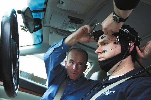 Russ Martin of AAA, is assisted by Joel Cooper, left, hooking the electroencephalographic (EEG)-configured skull cap to the research vehicle Tuesday during a demonstrations in support of their new ...
