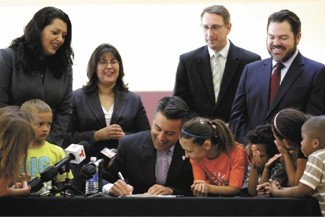 Nevada Gov. Brian Sandoval signs an English language learners funding bill Wednesday with Nevada lawmakers and local children at the Bill & Lillie Heinrich YMCA. The bill is significant for Clark  ...
