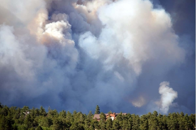 Thick smoke approaches a home as the Black Forest Fire burns northeast of Colorado Springs, Colo. The fire burned several homes and forced the evacuation of thousands of people.