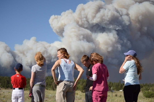 Neighbors watch as the Black Forest Fire burns northeast of Colorado Springs, Colo. The fire burned several homes and forced the evacuation of thousands of people.