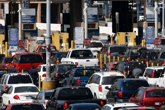 This 2009 file shows federal agents mixing into a swarm of automobiles as they do security checks on vehicles waiting to enter the United States at the San Ysidro Border Crossing in San Diego.
