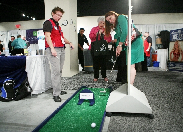 Hope Negro, far left, watches as Melody Kelly takes a golf shot for a prize Wednesday at the Lowe's booth during Business Expo 2013 in Las Vegas. The event offers a look at Las Vegas businesses th ...