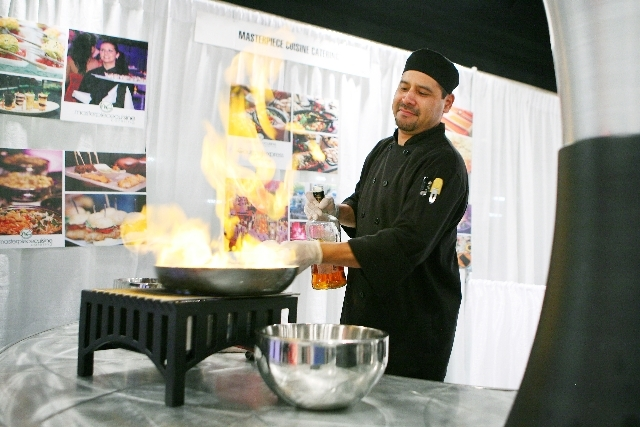 Executive Chef Cain David prepares doughnuts flambé on Wednesday at the Masterpiece Cuisine Catering booth at the Las Vegas Metro Chamber of Commerce Business Expo at the World Market Center.