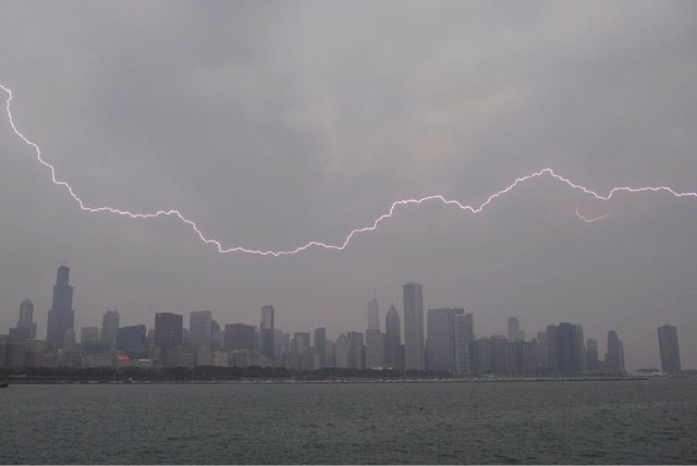 Lighting flashes over the Chicago skyline Wednesday. An unusually massive line of storms packing hail, lightning and tree-toppling winds was rolling through the Midwest on Wednesday and could affe ...