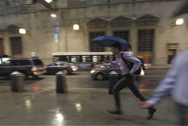 A pedestrian races to avoid an unusually massive line of storms packing hail, lightning and tree-toppling winds that have been forecast for evening rush hour Wednesday in Chicago.
