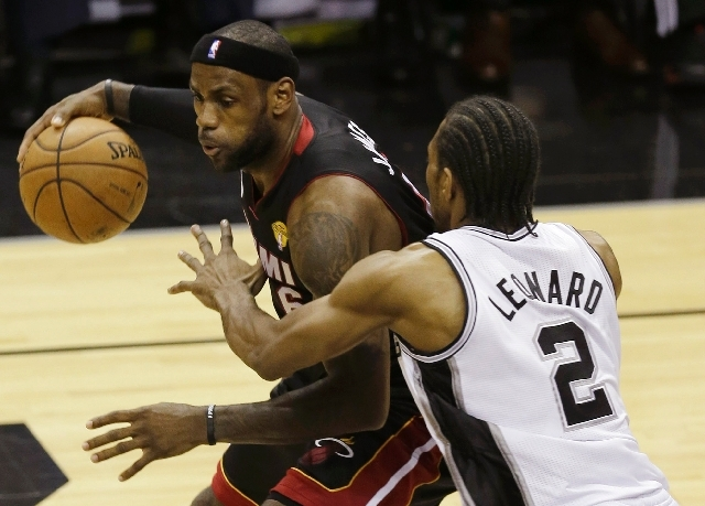 LeBron James of the Heat backs into the lane against Spurs defender Kawhi Leonard in the first half Thursday. James had 33 points to lead Miami's Finals-tying 109-93 victory.