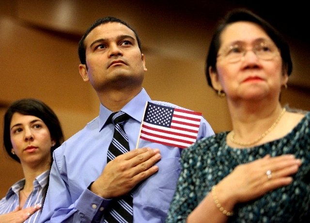 Samir Patel, center, originally from India, holds his hand over his heart during the national anthem at a naturalization ceremony at Las Vegas City Hall on Tuesday. Patel was one of about 200 peop ...