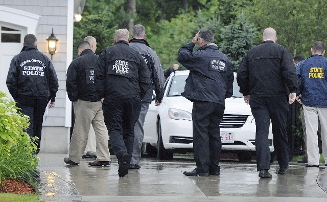 In this Tuesday, June 18 photo, state and local police gather outside the home of New England Patriot's NFL football player Aaron Hernandez in North Attleborough, Mass.  Police spent hours at the  ...
