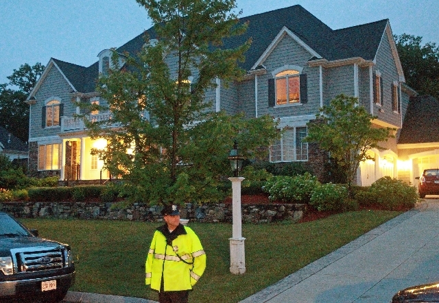 In this Tuesday, June 18 photo, a police officer stands outside the home of New England Patriot's NFL football player Aaron Hernandez in North Attleborough, Mass. State and local police spent hour ...