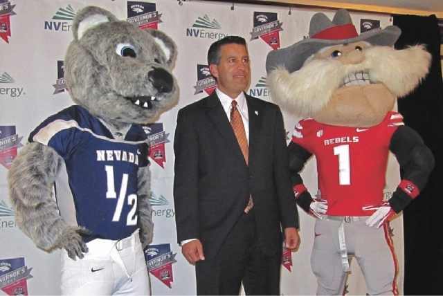 Nevada Gov. Brian Sandoval, center, poses with the mascots for UNR and UNLV.