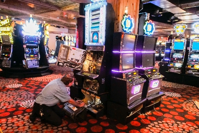Ken Ryder, a slot technician for Hooters Hotel, sets up phone lines to connect progressive slots Thursday after new carpeting was installed in the casino portion of Hooters Hotel in Las Vegas.