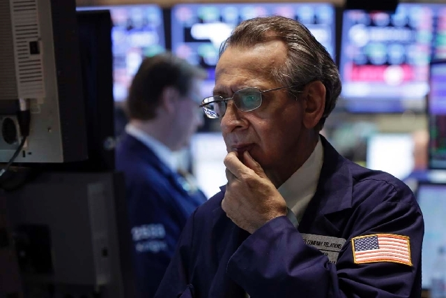 Specialist Joseph Quaglieri looks at a monitor as he works on the floor of the New York Stock Exchange on Thursday. Financial markets are sliding after the Federal Reserve said it could end its hu ...