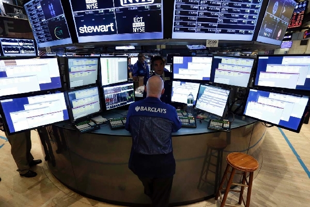 Specialist John O'Hara works at his post on the floor of the New York Stock Exchange on Thursday. As the markets slide, experts say there is a good case for staying calm and holding onto stocks.