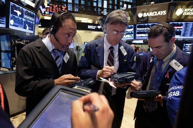 Traders gather at a post on the floor of the New York Stock Exchange on Thursday.