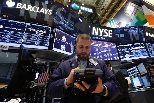Trader Michael Hagis works on the floor of the New York Stock Exchange on Thursday. Financial markets are sliding after the Federal Reserve said it could end its huge bond-buying program by the mi ...