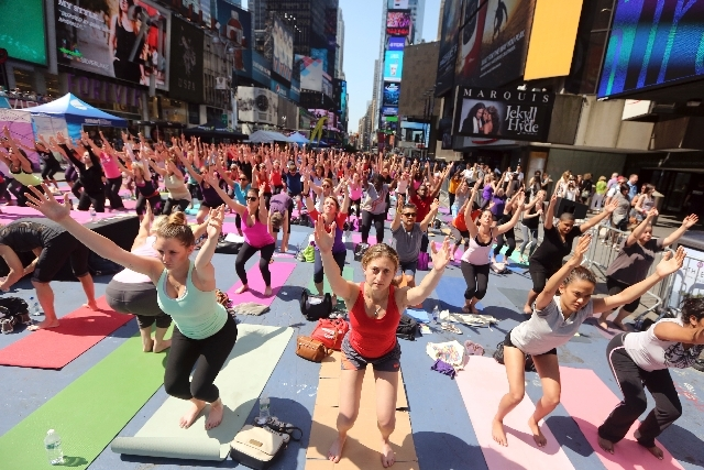 "People practice yoga in New York's Times Square on Friday. Yoga enthusiast marked the longest day of the year with five free ""Mind Over Madness"" yoga classes during the 11th annual Solstice in Tim ..."