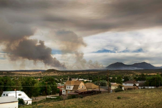 The East Peak fire burns in the afternoon on Friday near Walsenburg, Colo. The fire has burned more than 9,000 acres, and the people of Walsenburg, on pre-evacuation, continue to watch the fire's  ...